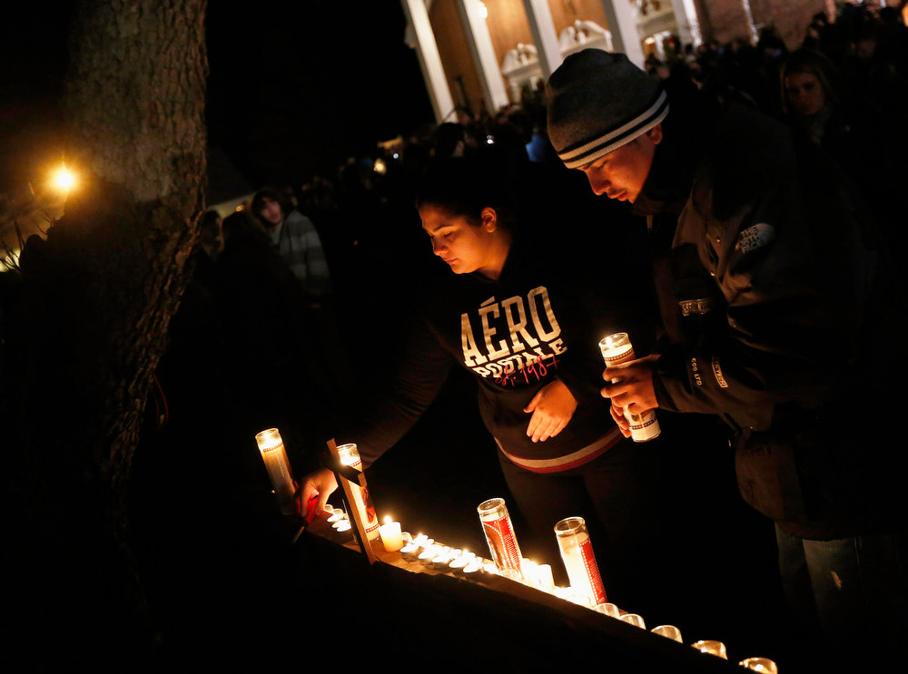 . People light candles outside a vigil at the Saint Rose of Lima church in Newtown, Connecticut December 14, 2012. The peace and security of the suburban Connecticut community of Newtown lay shattered on Friday after a gunman attacked a primary school in one of the worst mass shootings in U.S. History. Tearful parents and children gathered around Sandy Hook Elementary School by midday on Friday, surrounded by police vehicles, as young and old alike struggled to make sense of a shooting rampage that killed at least 28 people, including 20 children. REUTERS/Shannon Stapleton