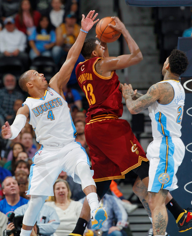 . Cleveland Cavaliers forward Tristan Thompson, center, pulls down a rebound between Denver Nuggets guard Randy Foye, left, and forward Wilson Chandler in the fourth quarter of an NBA basketball game in Denver, Friday, Jan. 17, 2014. The Cavaliers won 117-109. (AP Photo/David Zalubowski)