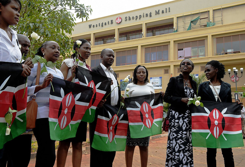. People hold Kenyan flags and white roses during a memorial ceremony to mark one year since the Westgate terrorist attack, outside the Westgate mall in Nairobi on September 21, 2014. At least 67 people were killed and scores wounded when a small group of Al-Qaeda affiliated fighters stormed the Westgate mall on September 21, 2013. CARL DE SOUZA/AFP/Getty Images