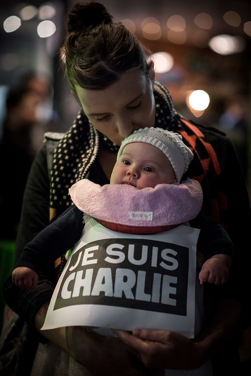 ". A French woman kisses her baby as she attends a vigil in solidarity with the victims of the shooting at the Paris office of the satirical newspaper Charlie Hebdo in Hong Kong on January 8, 2015. The UN Security Council led global condemnation of the ""terrorist\"" shooting at French magazine Charlie Hebdo which left 12 people dead, in a shocking attack on freedom of speech in Europe. AFP PHOTO / Philippe  LOPEZ/AFP/Getty Images"