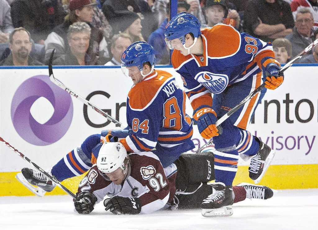 . Colorado Avalanche\'s Gabriel Landeskog (92) is knocked down by Edmonton Oilers\' Oscar Klefbom (84) and Ryan Nugent-Hopkins (93) during first period NHL hockey action in Edmonton, Alberta, on Tuesday April 8, 2014. (AP Photo/The Canadian Press, Jason Franson)
