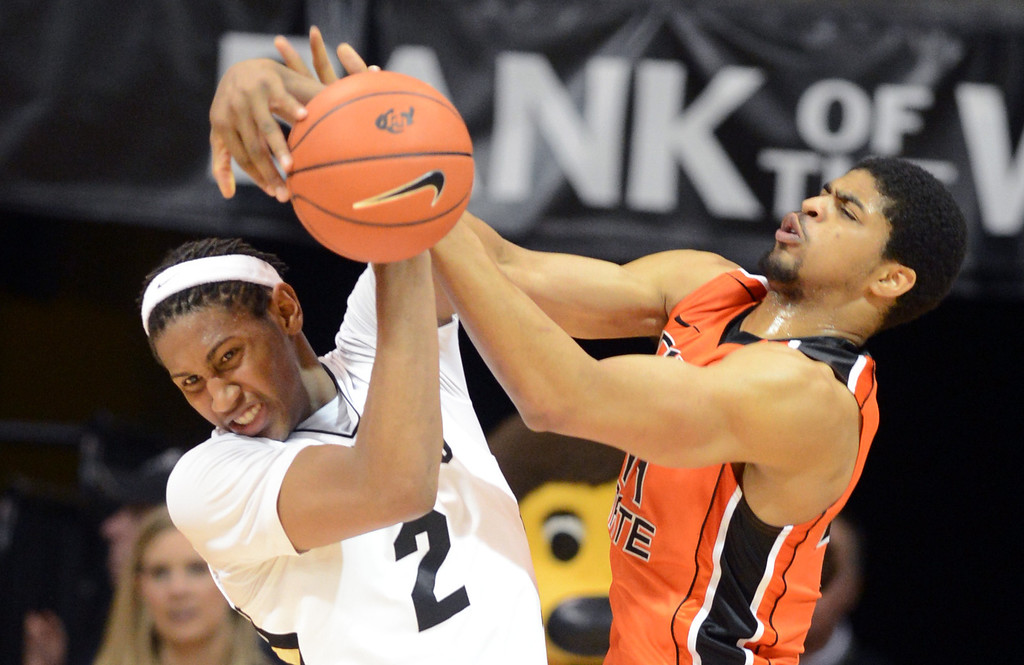 . Xavier Johnson, left, of Colorado, and Devon Collier of Oregon State try to control a rebound during the first half of the March 9, 2013 game in Boulder.    (Cliff Grassmick/Boulder Daily Camera)