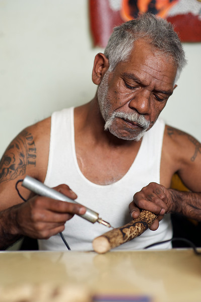 Aboriginal artist at work, burning a design in a message stick