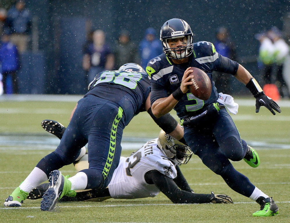 . SEATTLE, WA - JANUARY 11:  Quarterback Russell Wilson #3 of the Seattle Seahawks runs the ball against the New Orleans Saints in the second quarter during the NFC Divisional Playoff Game at CenturyLink Field on January 11, 2014 in Seattle, Washington.  (Photo by Harry How/Getty Images)