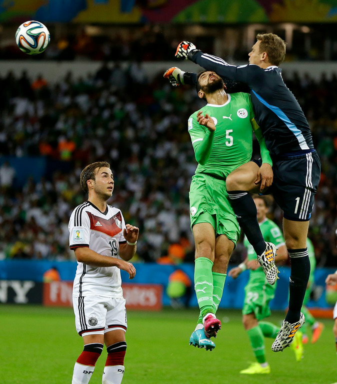 . Germany\'s goalkeeper Manuel Neuer. right, punches the ball away from Algeria\'s Rafik Halliche during the World Cup round of 16 soccer match between Germany and Algeria at the Estadio Beira-Rio in Porto Alegre, Brazil, Monday, June 30, 2014. (AP Photo/Kirsty Wigglesworth)
