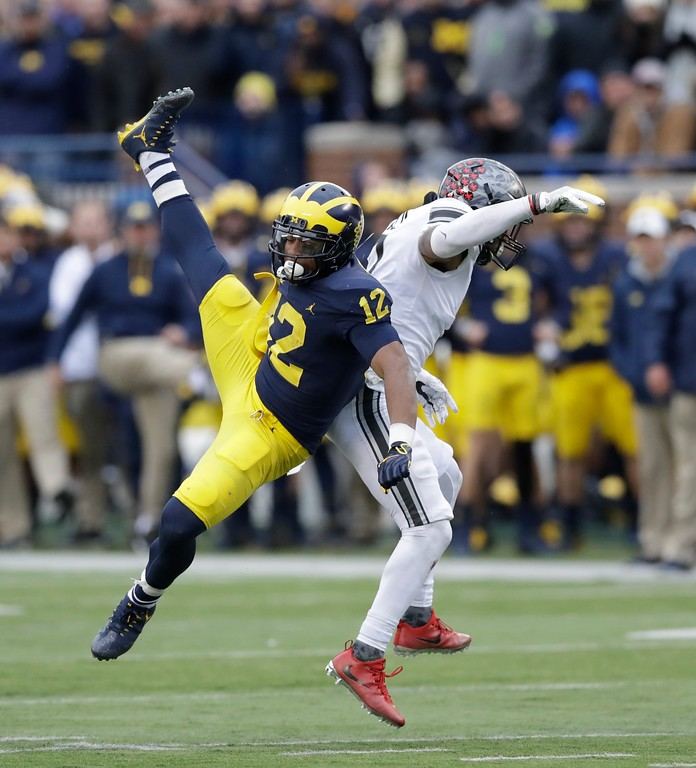 . Michigan running back Chris Evans (12) and Ohio State safety Damon Webb (7) collide at midfield during the second half of an NCAA college football game, Saturday, Nov. 25, 2017, in Ann Arbor, Mich. (AP Photo/Carlos Osorio)