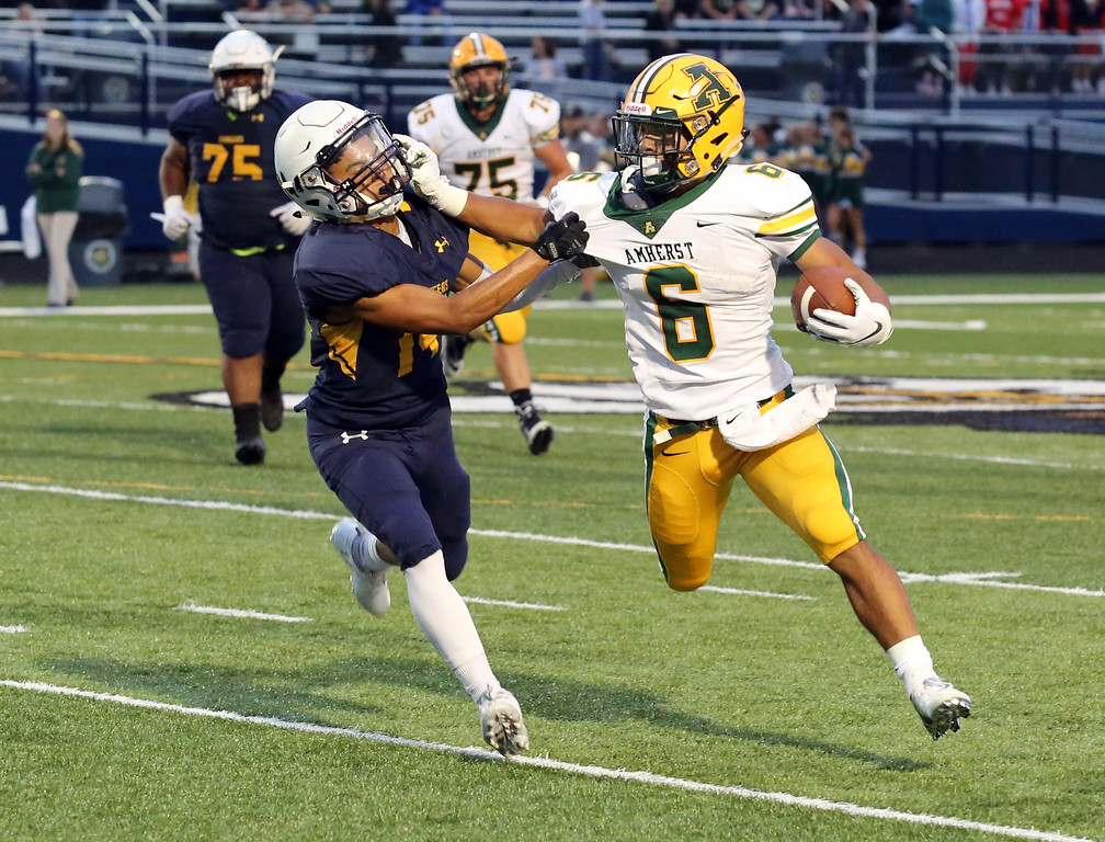 . David Schneider - The Morning Journal<br> Amherst\'s Khennedy Scagliozzo stiff arms Marcus McLean of North Ridgeville during a second quarter run on Sept. 7.