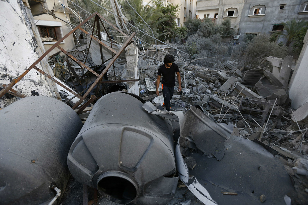 . A Palestinian youth inspects a house after it was destroyed by an Israeli air strike early on July 16, 2014, in Gaza City. New Israeli air and tank strikes in Gaza early today killed several people, medics said, bringing the death toll from Israel\'s operation in the besieged Palestinian territory to 204. AFP PHOTO / MOHAMMED ABED/AFP/Getty Images