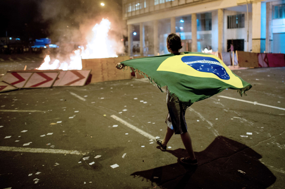 . A demonstrator walks with a Brazilian flag late on June 19, 2013 in the center of Niteroi, 10 kms from Rio de Janeiro. Protesters battled police late on June 19, even after Brazil\'s two biggest cities rolled back the transit fare hikes that triggered two weeks of nationwide protests.  The fare rollback in Sao Paulo and Rio de Janeiro marked a major victory for the protests, which are the biggest Brazil has seen in two decades.   CHRISTOPHE SIMON/AFP/Getty Images
