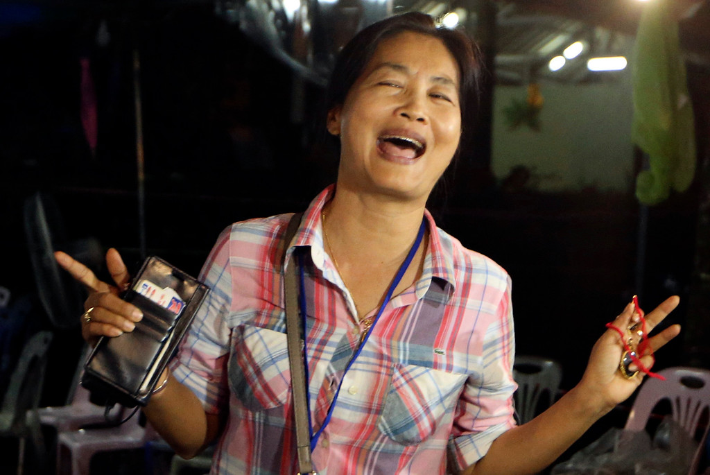 . A family member smiles after hearing the news that the missing 12 boys and their soccer coach have been found, in Mae Sai, Chiang Rai province, in northern Thailand, Monday, July 2, 2018. A Thai provincial governor says all 12 boys and their coach have been found alive in the cave where they went missing over a week ago in northern Thailand. (AP Photo/Sakchai Lalit)