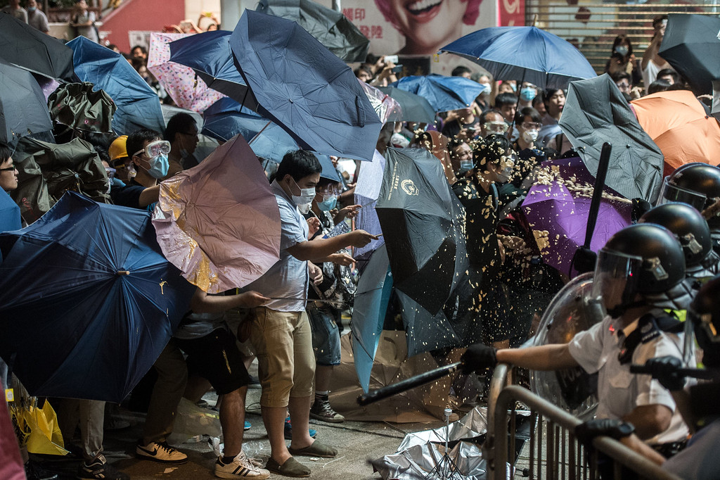 . TOPSHOTS Police use pepper spray against pro-democracy protesters using raised umbrellas for protection during a clash in the Mongkok district of Hong Kong late on October 17, 2014. Fresh clashes broke out in Hong Kong on October 17 as pro-democracy demonstrators attempted to take back a protest camp in a densely populated suburb that had been partially cleared by police earlier in the day.    AFP PHOTO / ANTHONY WALLACEANTHONY WALLACE/AFP/Getty Images