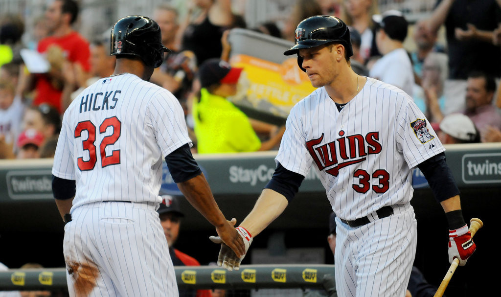 . Aaron Hicks is welcomed home by Justin Morneau after scoring on Joe Mauer\'s single during the third inning. (Pioneer Press: John Autey)