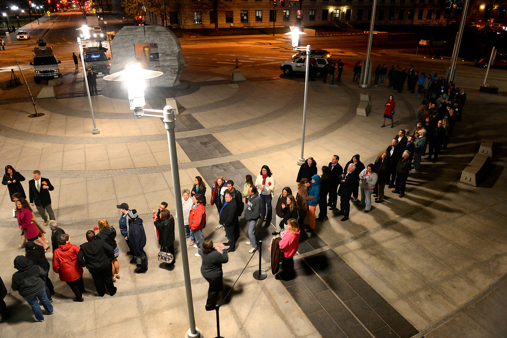""". Couples, friends and family members wait to enter the Wellington E. Webb Municipal Office Building in Denver on April 30, 2013. The Clerk and Recorder\'s Office opened for business from midnight to 3 a.m. to issue civil union licenses to couples on May 1, 2013, when the Civil Union Act became law. The excitement was palpable among the friends and family who gathered to witness. \""""It\'s a proud night for my family,\"""" said Juan Moreno, who came to support his daughter, Hillary. \""""It\'s not right it took so long, because people shouldn\'t judge. Love is a hard enough thing to find.\"""""""
