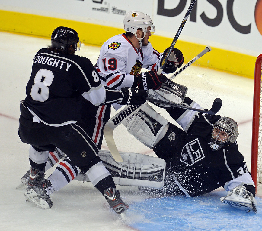 . Kings\' goalie Jonathan Quick  #32 gets tied up with the Blackhawks\' Jonathan Toews #19 as Drew Doughty #8 moves in during the 1st period of game 4 of the Western Conference finals at the Staples Center in Los Angeles June 6, 2013. (David Crane/Los Angeles Daily News)