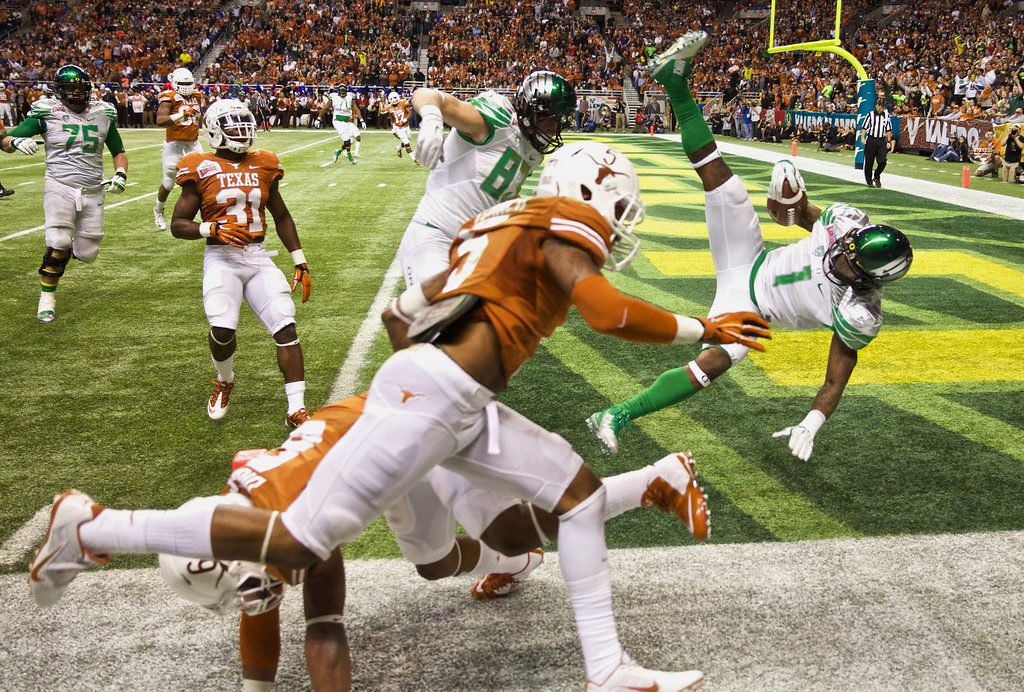 . Oregon Ducks wide receiver Josh Huff (1) flies into the end zone in last seconds of the second quarter to make the score 20-7 against the Texas Longhorns in the Valero Alamo Bowl NCAA college football game in San Antonio, Texas, at the Alamodome, Mon, Dec 30, 2013.    (AP Photo/The Oregonian, Thomas Boyd)