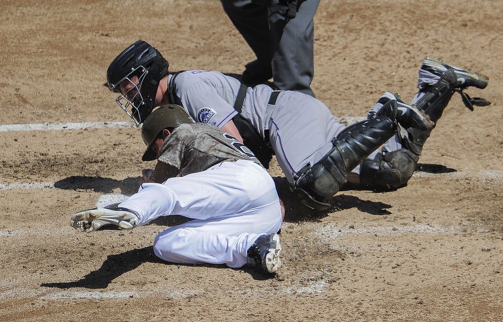. Reymond Fuentes #27 of the San Diego Padres is tagged out at the plate by Jordan Pacheco #15 of the Colorado Rockies during the third inning of a baseball game at Petco Park on September 8, 2013 in San Diego, California.  (Photo by Denis Poroy/Getty Images)