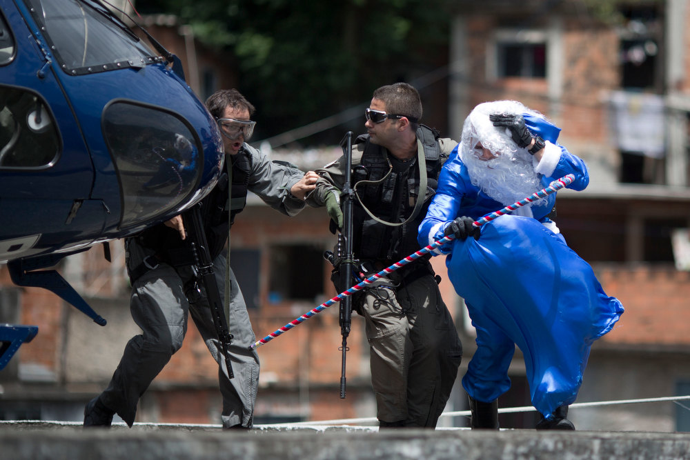 Description of . A police officer dressed in a blue Santa Claus costume braces against the wind as he is escorted out of a helicopter as he arrives to the Macacos slum in Rio de Janeiro, Brazil, Thursday, Dec. 20, 2012. The Pacifying Police Unit, or UPP, organized for Santa to visit the pacified slum to hand out Christmas gifts to young residents. (AP Photo/Felipe Dana)