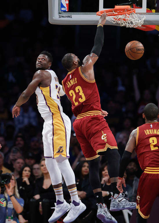 . Cleveland Cavaliers\' LeBron James, center, dunks past Los Angeles Lakers\' Julius Randle during the first half of an NBA basketball game Sunday, March 19, 2017, in Los Angeles. (AP Photo/Jae C. Hong)