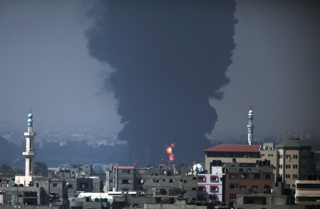 . Seen from Gaza City, smoke and flames rise from Gaza\'s electricity distribution company plant after it was hit by Israeli strikes in the Nusseirat refugee camp, central Gaza Strip,Tuesday, July 29, 2014.  (AP Photo/Lefteris Pitarakis)
