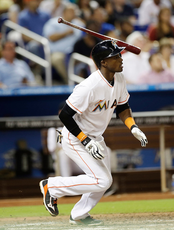 . Miami Marlins batter Adeiny Hechavarria tosses his bat as he watches his ball after hitting a fourth inning triple that drove one run home during a baseball game against the Colorado Rockies, Saturday, Aug. 24, 2013, in Miami,. (AP Photo/J Pat Carter)