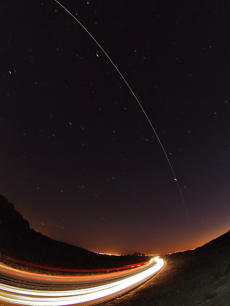 Aug 20 2011. 2146 hrs super bright pass of the ISS. This time we had crystal clear skies :-) Directly overhead so I located my local east/west trunk road and set up the car trails shot with 2 cameras. This one captured with Olympus E5 7 8mm fisheye. F5, ISO 500 and approx 9 15s exposures stacked to produce this.