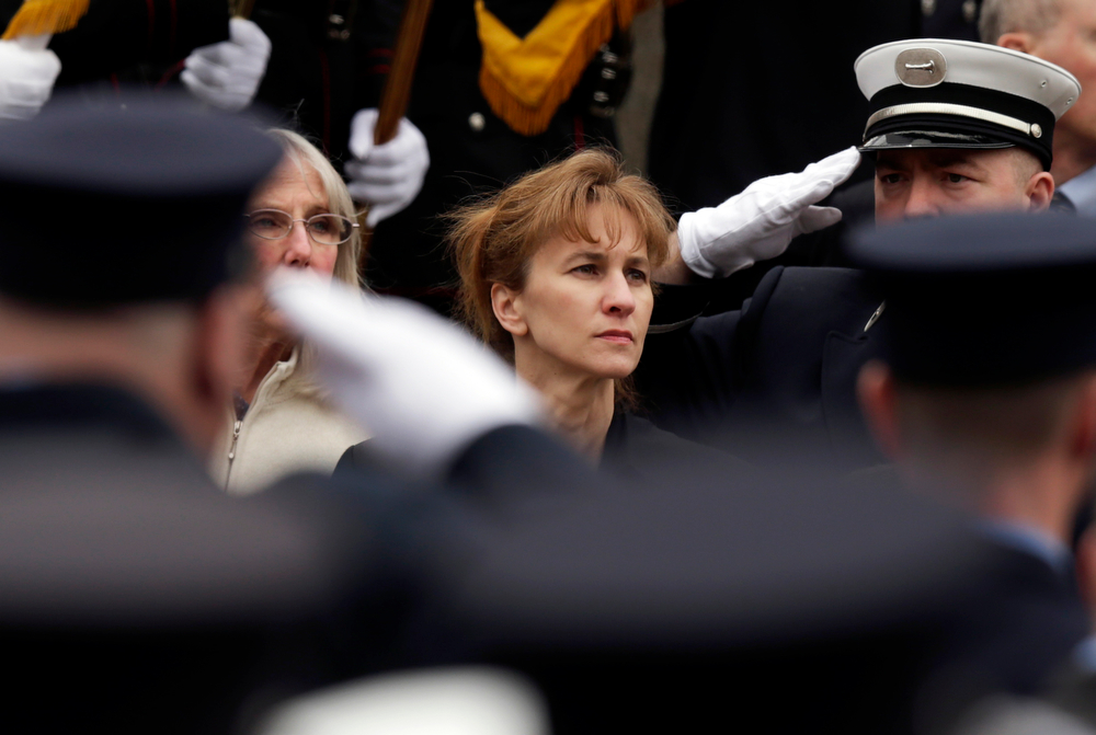 . Firefighters salute as Kristen Walsh watches the casket of her late-husband Boston Fire Lt. Edward Walsh is lifted onto Engine 33 as the funeral procession prepares to depart St. Patrick\'s Church in Watertown, Mass., Wednesday, April 2, 2014. Walsh and his colleague Michael Kennedy died after being trapped while battling a nine-alarm apartment fire in Boston on March 26. (AP Photo/Charles Krupa)