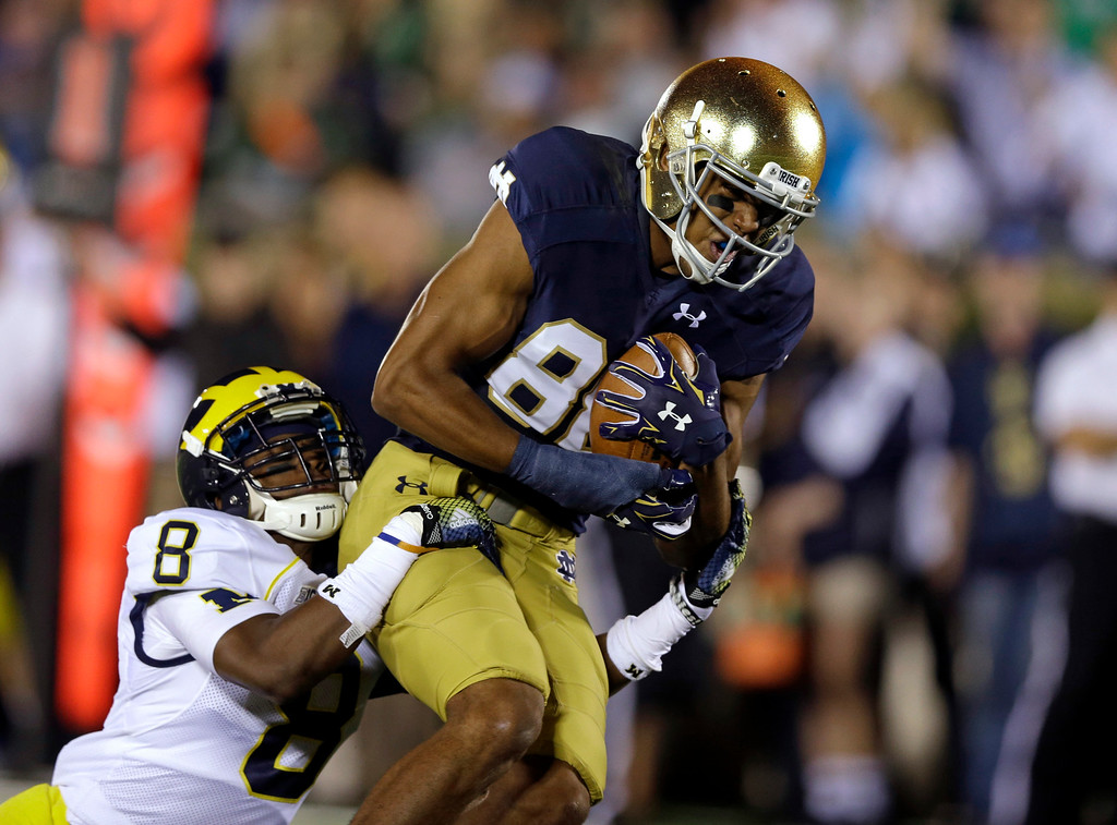 . Notre Dame wide receiver Corey Robinson is tacked by Michigan defensive back Channing Stribling on the 1-yard line during the first half of an NCAA college football game in South Bend, Ind., Saturday, Sept. 6, 2014. (AP Photo/Michael Conroy)