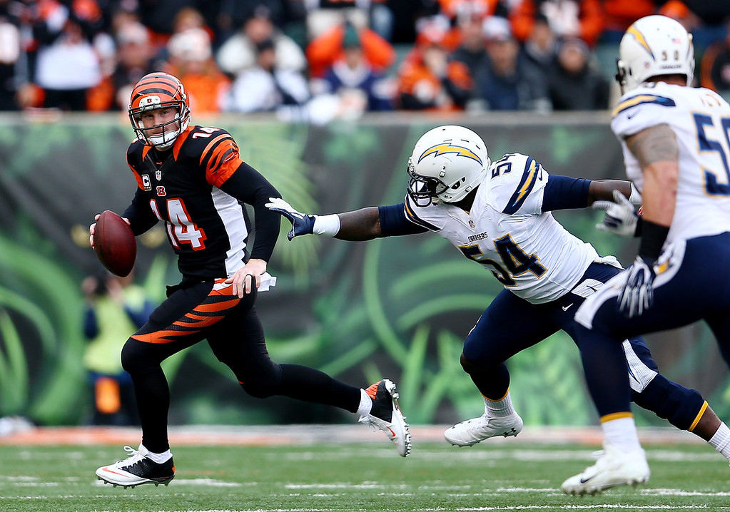 . Quarterback Andy Dalton #14 of the Cincinnati Bengals is pressured by outside linebacker Melvin Ingram #54 of the San Diego Chargers during a Wild Card Playoff game at Paul Brown Stadium on January 5, 2014 in Cincinnati, Ohio.  (Photo by Andy Lyons/Getty Images)