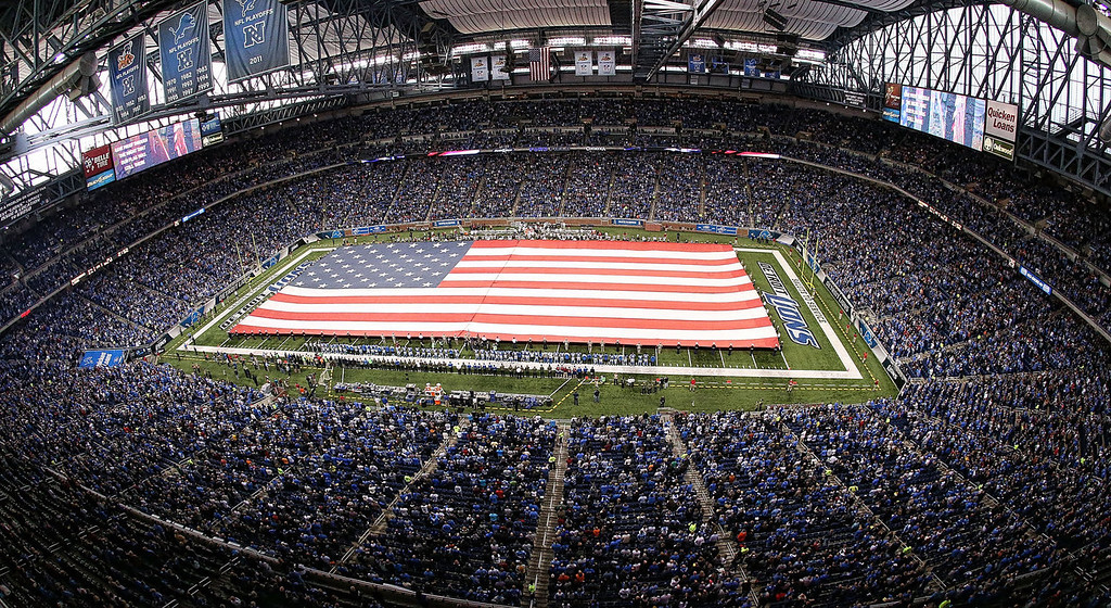 . A large American flag in unfurled during the National Anthem prior to the start of the game between the Tampa Bay Buccaneers and the Detroit Lions at Ford Field on November 24, 2013 in Detroit, Michigan.  (Photo by Leon Halip/Getty Images)