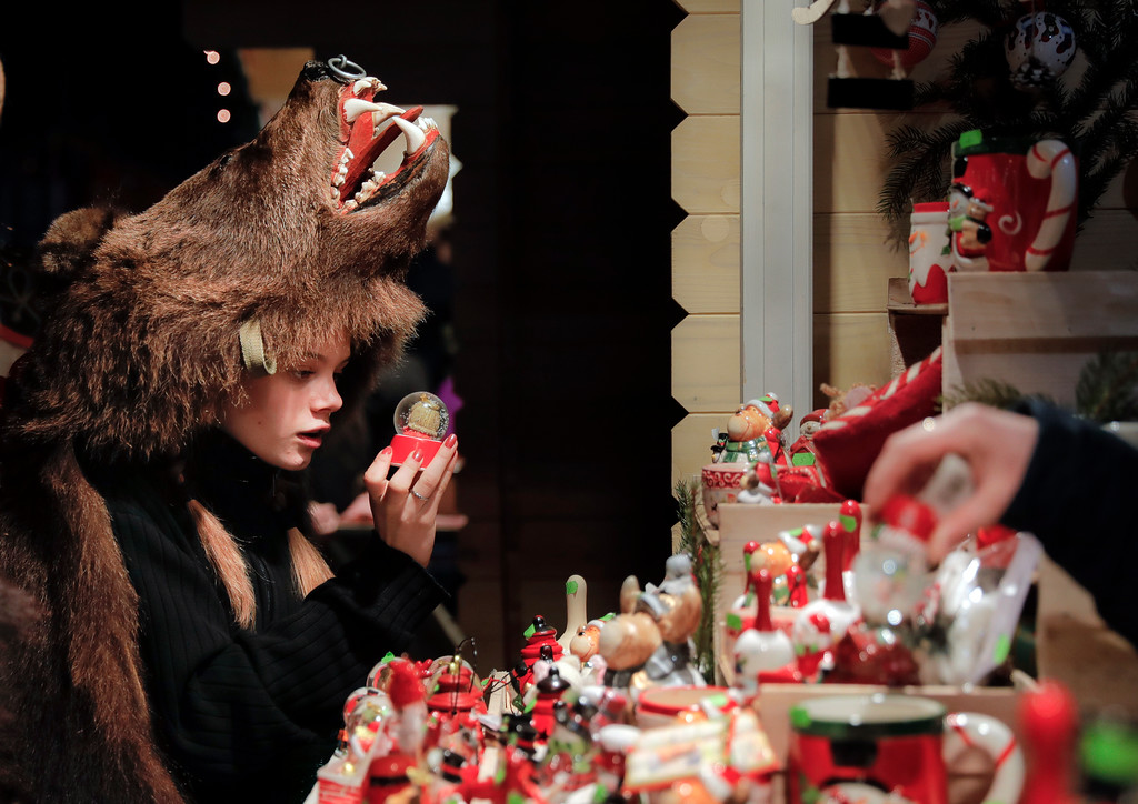 . In this Thursday, Dec. 28, 2017, picture Raluca Atrejei, wearing a bear fur costume, looks at an item in a Christmas fair, in Piatra Neamt, Romania. Hundreds of people descend on the sleepy northern Romanian city of Comanesti every year dressed head to toe like bears, in costumes made from real fur, with the heads attached. It\'s a tradition that originated in pre-Christian times, when dancers wearing colored costumes or animal furs went from house to house in villages, singing and dancing to ward off evil. .(AP Photo/Vadim Ghirda)