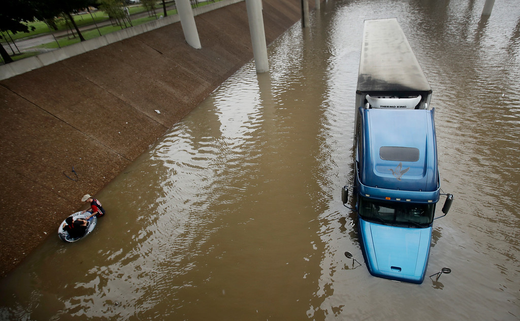 . An unidentified man helps Carlos Torres, in tube, get to dry ground after Torres drove his tractor-trailer into a freeway flooded by Tropical Storm Harvey on Sunday, Aug. 27, 2017, near downtown Houston, Texas. (AP Photo/Charlie Riedel)