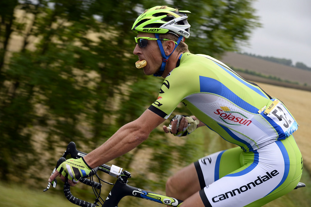 . Poland\'s Maciej Bodnar eats as he rides during the 234.5 km seventh stage of the 101st edition of the Tour de France cycling race on July 11, 2014 between Epernay and Nancy, northeastern France.  AFP PHOTO / LIONEL BONAVENTURE/AFP/Getty Images