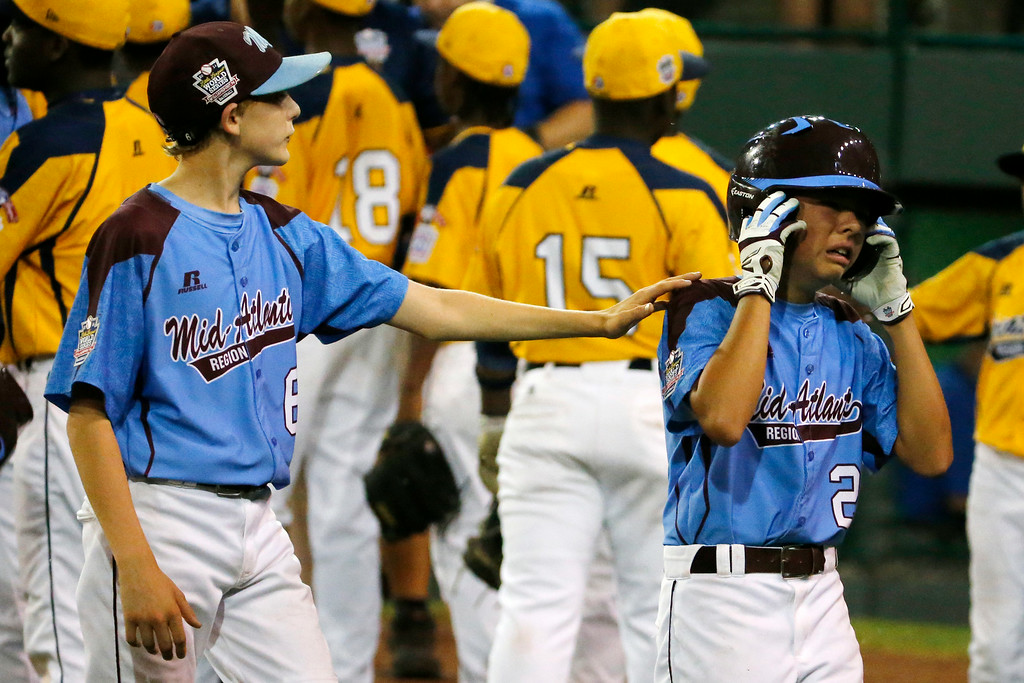 . Philadelphia\'s  Erik Lipson, left, tries to comfort teammate Jack Rice (2) after a 6-5 loss in an elimination baseball game against Chicago at the Little League World Series tournament in South Williamsport, Pa., Thursday, Aug. 21, 2014. (AP Photo/Gene J. Puskar)