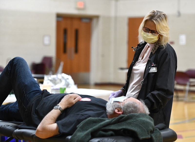 4/8/2020 Mike Orazzi | Staff David Bass while donating blood with the Red Cross' Carol Lessard at the Wheeler Regional YMCA in Plainville on Wednesday.