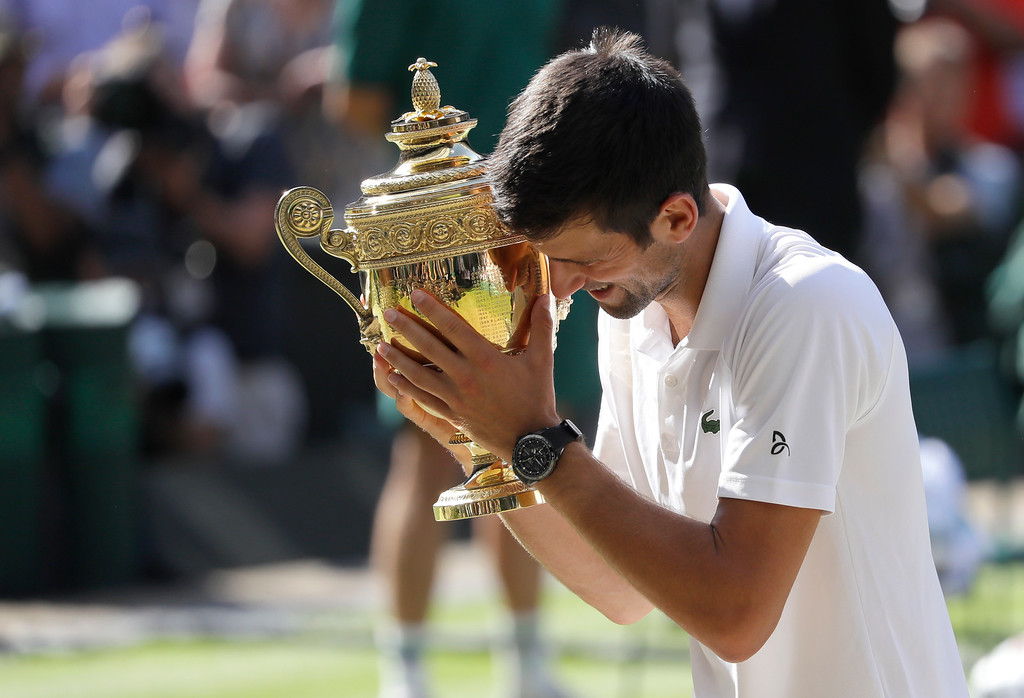 . Serbia\'s Novak Djokovic holds the trophy after winning the men\'s singles final match against Kevin Anderson of South Africa, at the Wimbledon Tennis Championships, in London, Sunday July 15, 2018.(AP Photo/Kirsty Wigglesworth)