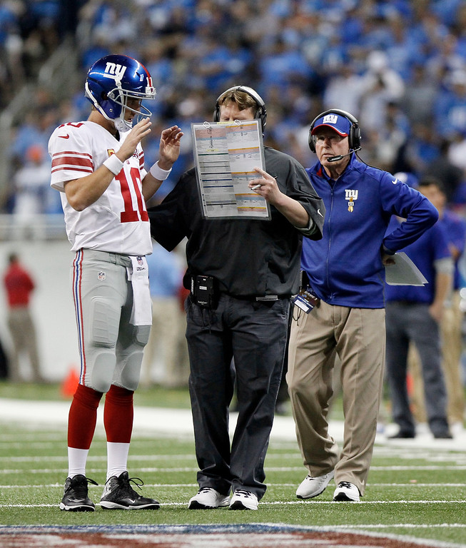 . New York Giants quarterback Eli Manning (10) talks with offensive coordinator Ben Mcadoo during the second quarter of an NFL football game against the Detroit Lions in Detroit, Monday, Sept. 8, 2014. (AP Photo/Duane Burleson)