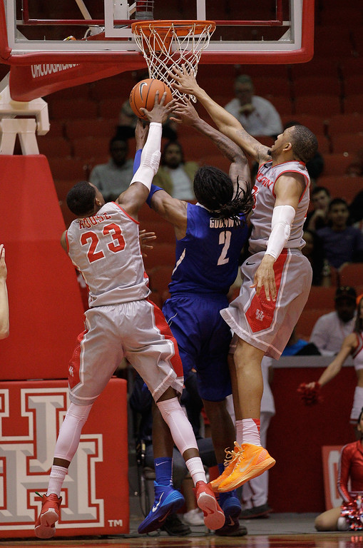 . Memphis\' forward Shaq Goodwin (2) attempts to drive to the basket through Houston\'s Danuel House (23) and Houston\'s TaShawn Thomas, right, during the second half of an NCAA college basketball game, Thursday, Feb. 27, 2014, in Houston. Houston won 77-68. (AP Photo/Bob Levey)