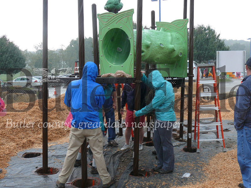 Volunteers work to put a piece of playground equipment in place Thursday at North Boundary Park in Cranberry Township.
