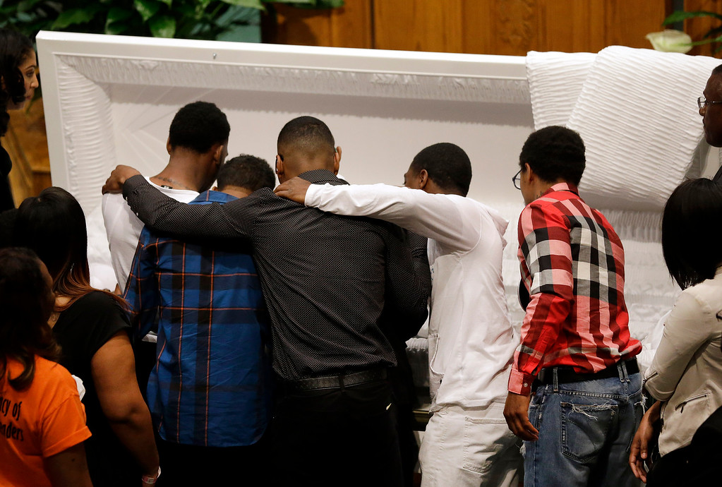. Mourners embrace as they gather in front of the casket containing the body of Freddie Gray before his funeral, Monday, April 27, 2015, at New Shiloh Baptist Church in Baltimore. Gray died from spinal injuries about a week after he was arrested and transported in a Baltimore Police Department van. (AP Photo/Patrick Semansky)