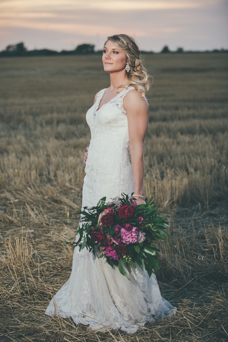 A newlywed bride wearing a lace wedding dress standing in a field at sunset holding her red and pink bouquet on her wedding night