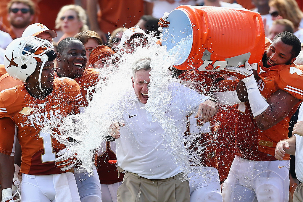 . Head coach Mack Brown of the Texas Longhorns has a cooler of ice water dumped on him by his team after the Longhorns beat the Oklahoma Sooners 36-20 at the Cotton Bowl on October 12, 2013 in Dallas, Texas.  (Photo by Tom Pennington/Getty Images)