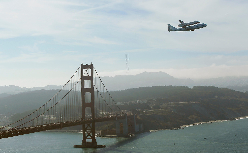 . Retired space shuttle Endeavor is carried on the back of a NASA jet as it approaches the Golden Gate Bridge in San Francisco, California September 21, 2012. Endeavor will be moved to its permanent home at the California Science Center mid-October.  REUTERS/Robert Galbraith