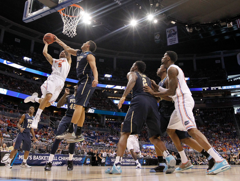 . Scottie Wilbekin #5 of the Florida Gators goes up for a shot against James Robinson #0 of the Pittsburgh Panthers in the first half during the third round of the 2014 NCAA Men\'s Basketball Tournament at Amway Center on March 22, 2014 in Orlando, Florida.  (Photo by Mike Ehrmann/Getty Images)