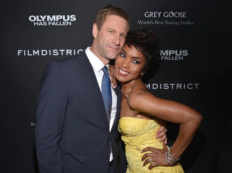 """. Actors Aaron Eckhart (L) and Angela Bassett arrive at the premiere of FilmDistrict\'s \""""Olympus Has Fallen\"""" at ArcLight Cinemas Cinerama Dome on March 18, 2013 in Hollywood, California.  (Photo by Alberto E. Rodriguez/Getty Images)"""