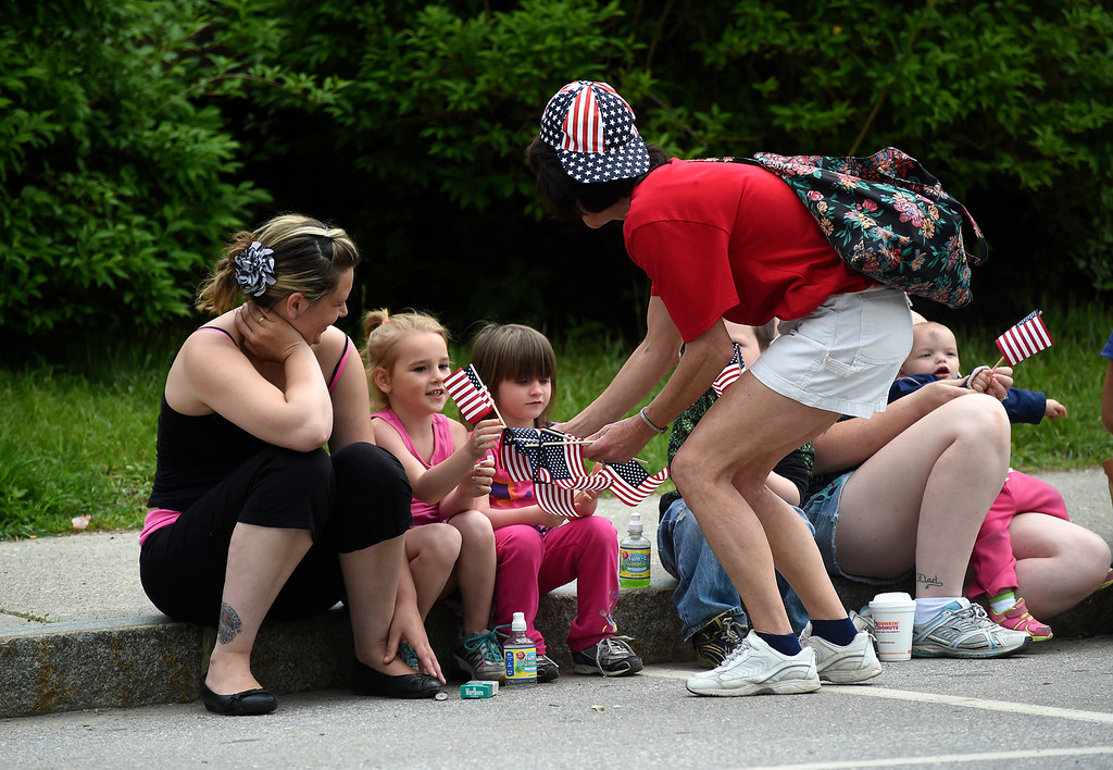 . Kayla Rice/Reformer Karen Johnson hands out flags to cousins Hayla and Maddison Paligo, both 4, before the Hinsdale Memorial Day parade on Monday morning.