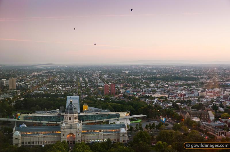 Hot air balloons beyond the Royal Exhibition Building and Carlton Gardens