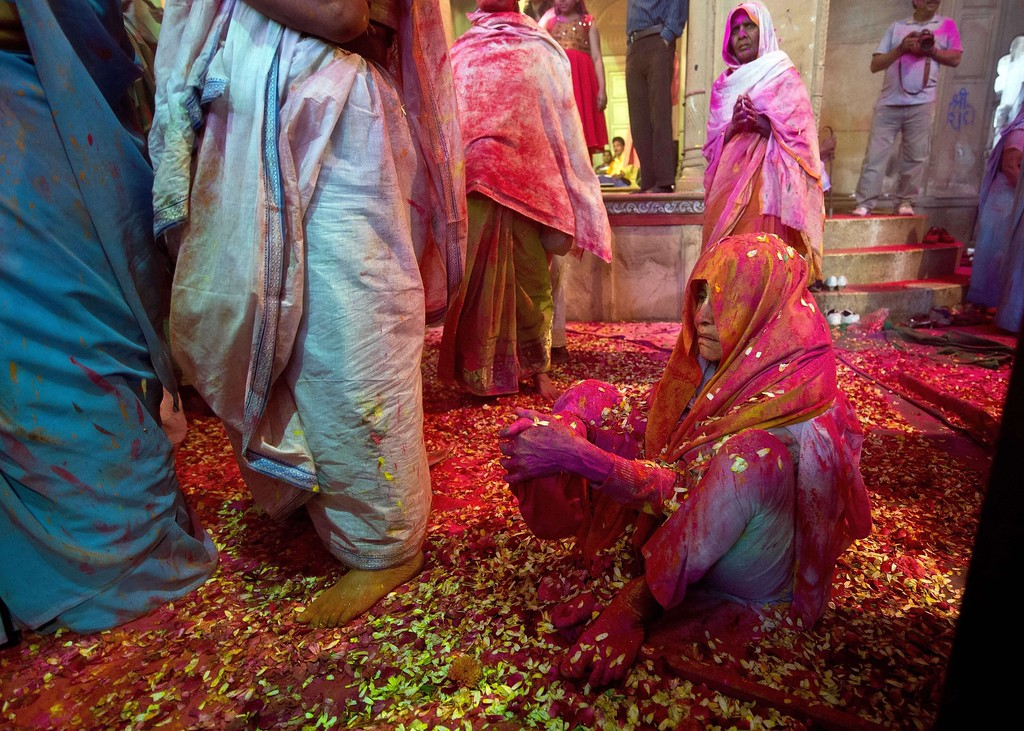 . An Indian widow, smeared in gulal (colored powder), prays during Holi celebrations in Vrindavan on March 14, 2014.  AFP PHOTO/Prakash SINGH/AFP/Getty Images