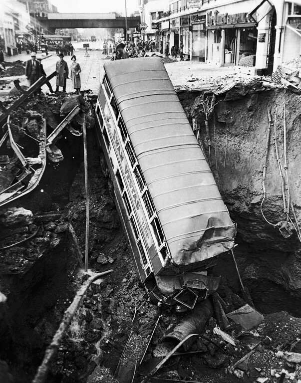 . This unusual view of a bus nosed into a huge bomb crater in a London street, was made after one of last year?s heavy night air raids of 1941.   The omnibus seen in the crater in a London Suburban street  in photo released on Jan. 23, 1942. (AP Photo)