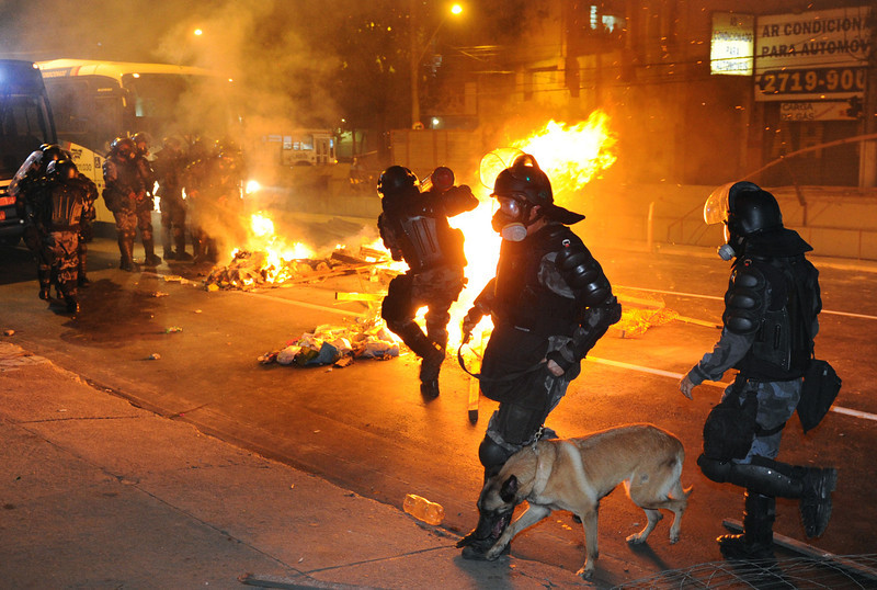 . Riot policemen try to extinguish a fire barricade set up by demonstrators in downtown Niteroi, near Rio de Janeiro, on June 19, 2013, during a protest against the $15 billion being spent on this month\'s Confederations Cup and the 2014 World Cup. Protests initially sparked by a hike in bus fares in Sao Paulo last week, quickly spiraled into nationwide marches against corruption, fueled by anger that -- in a country with a wide rich-poor divide -- billions of dollars were being spent on stadiums and far too little was earmarked for social programs.    TASSO MARCELO/AFP/Getty Images
