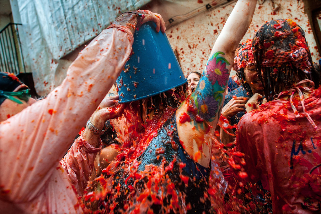 . Revelers celebrate covered by tomato pulp while participating the annual Tomatina festival on August 28, 2013 in Bunol, Spain. An estimated 20,000 people threw 130 tons of ripe tomatoes in the world\'s biggest tomato fight held annually in this Spanish Mediterranean town.  (Photo by David Ramos/Getty Images)
